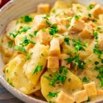 A bowl of crock pot scalloped potatoes with parsley on it