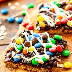 Bars topped with chocolate, m&m's, and white chocolate on wooden cutting board