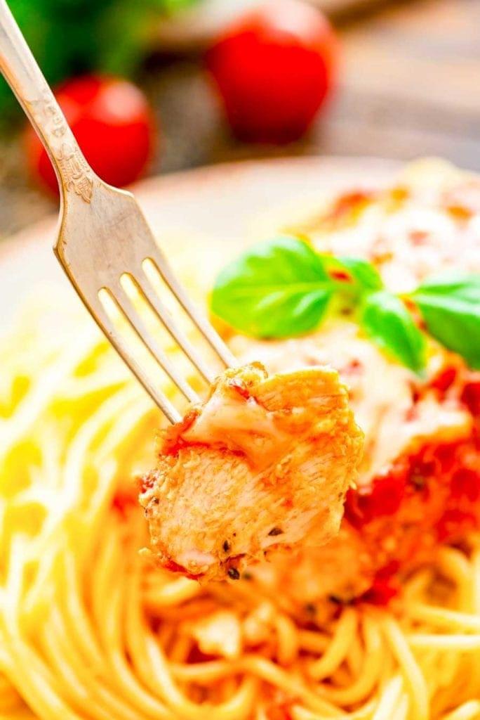 Piece of crock pot chicken Parmesan on fork