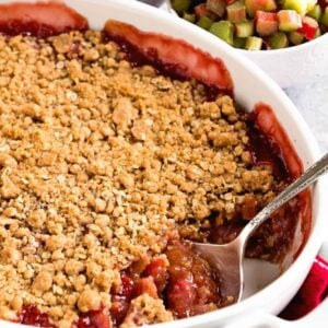 White casserole pan of strawberry rhubarb crisp next to two small bowls of strawberries and rhubarb