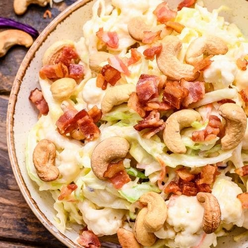 Overhead picture of cashew coleslaw in bowl topped with bacon and cashews