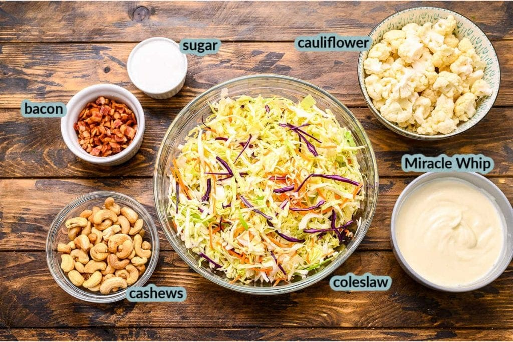 Overhead image showing coleslaw mix cashews miracle whip cauliflower bacon and sugar
