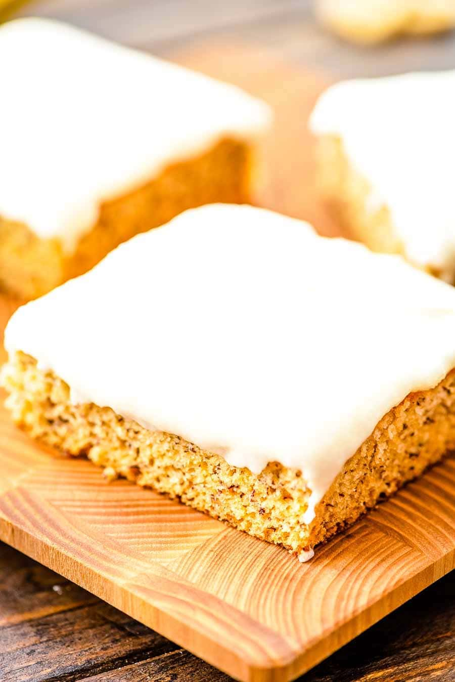 Square Slices of Frosted Banana Bars on cutting board