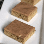 Three cinnamon frosted zucchini bars on a white plate