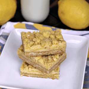 Three lemon crumb bar stacked on a white plate in front of two lemons and a glass of milk
