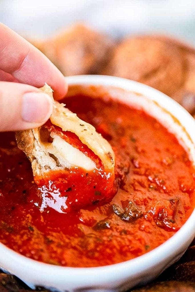 A cut open piece of pizza monkey bread being dipped in marinara sauce