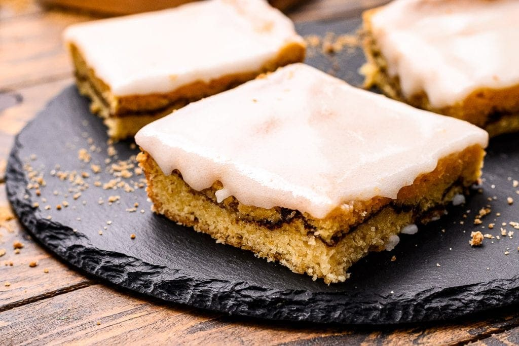 Cut Snickerdoodle Bars with frosting on a black slate piece