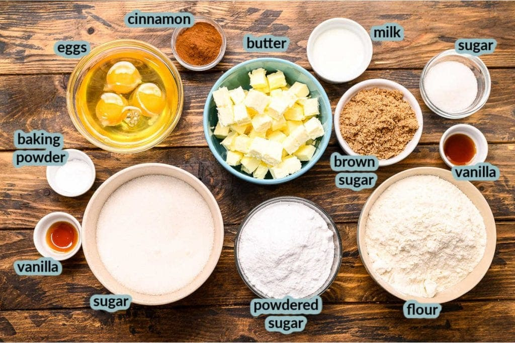 Overhead image showing all the ingredients to make Snickerdoodle Bars in cups eggs, butter cinnamon, flour, sugar, vanilla and more