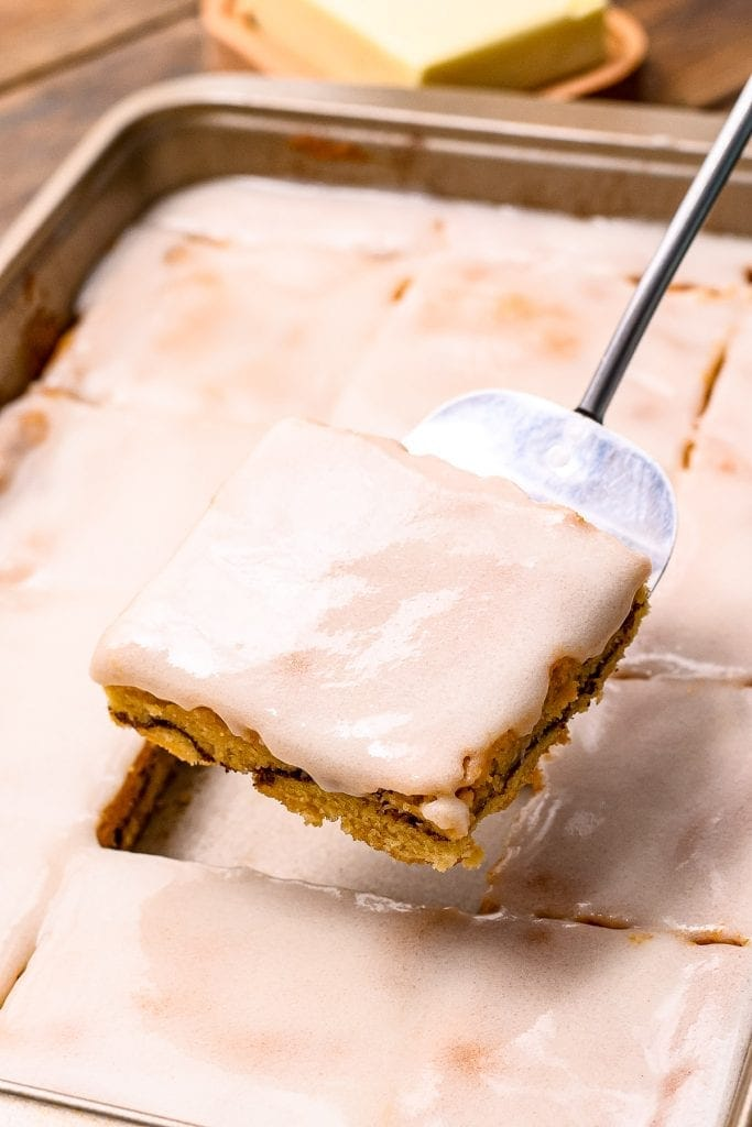 Metal spatula holding Snickerdoodle Bar above the pan of bars with frosting
