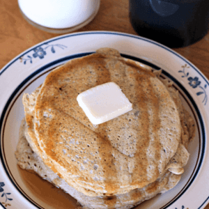 A short stack of zucchini bread pancakes topped with a pad of butter and syrup on a white plate in front of a glass of milk and a mug of coffee