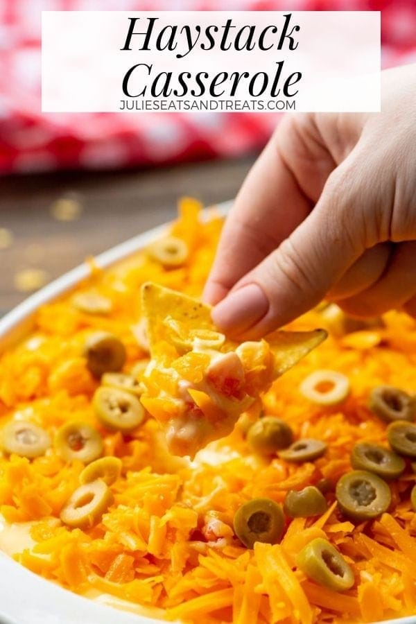 Hand dipping a chip into haystack casserole