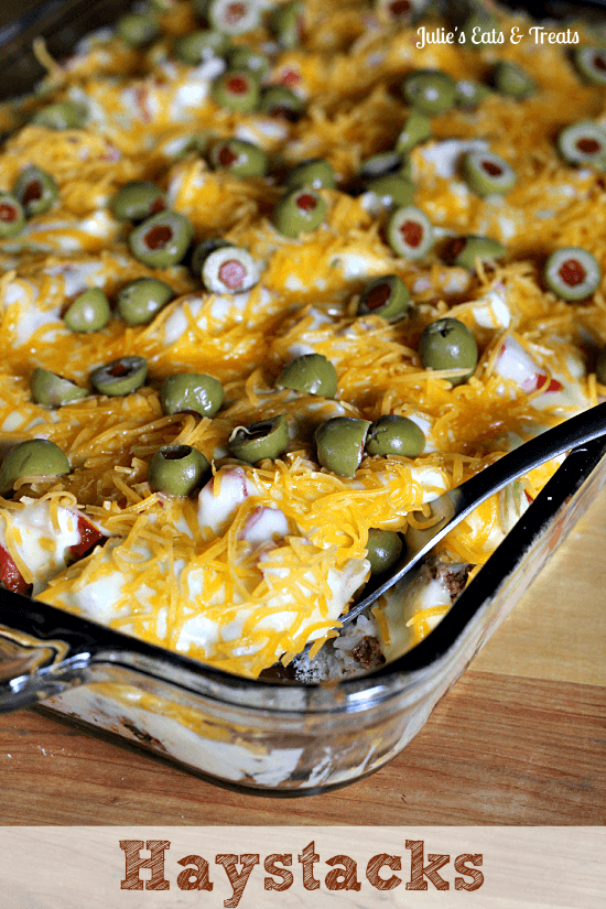 Haystacks ~ Yummy casserole full of rice and taco meat, topped with a cheese sauce, lettuce, tomatoes and olives! via www.julieseatsandtreats.com