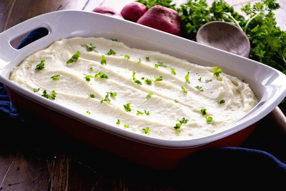 A casserole dish of mashed potatoes, a recipe for making mashed potatoes ahead of time.