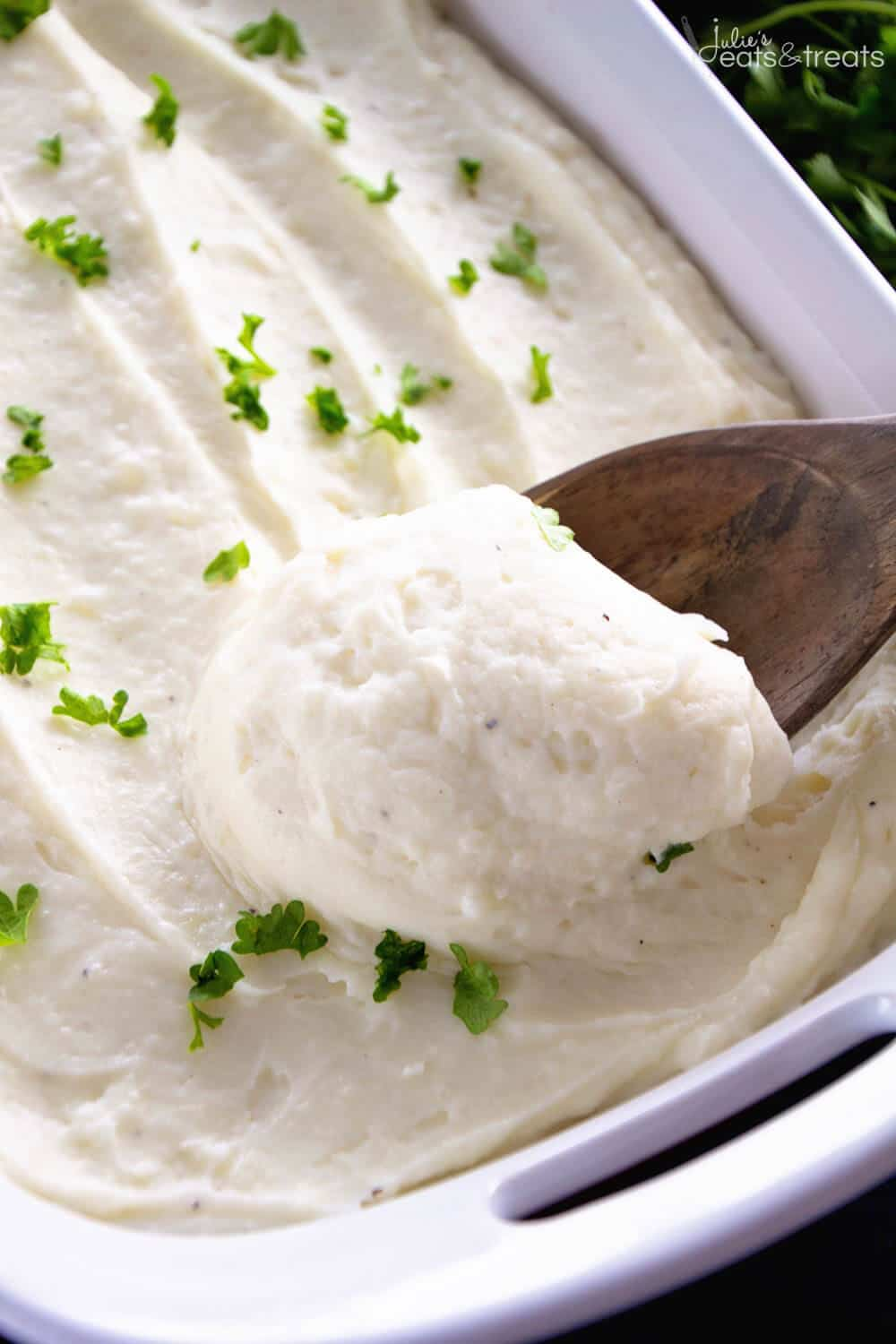 A spoonful of. mashed potatoes with cream cheese in a casserole dish topped with minced parsley.