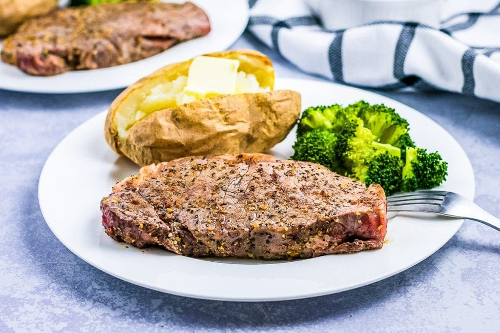 Seasoned steak on a white plate with baked potato and broccoli
