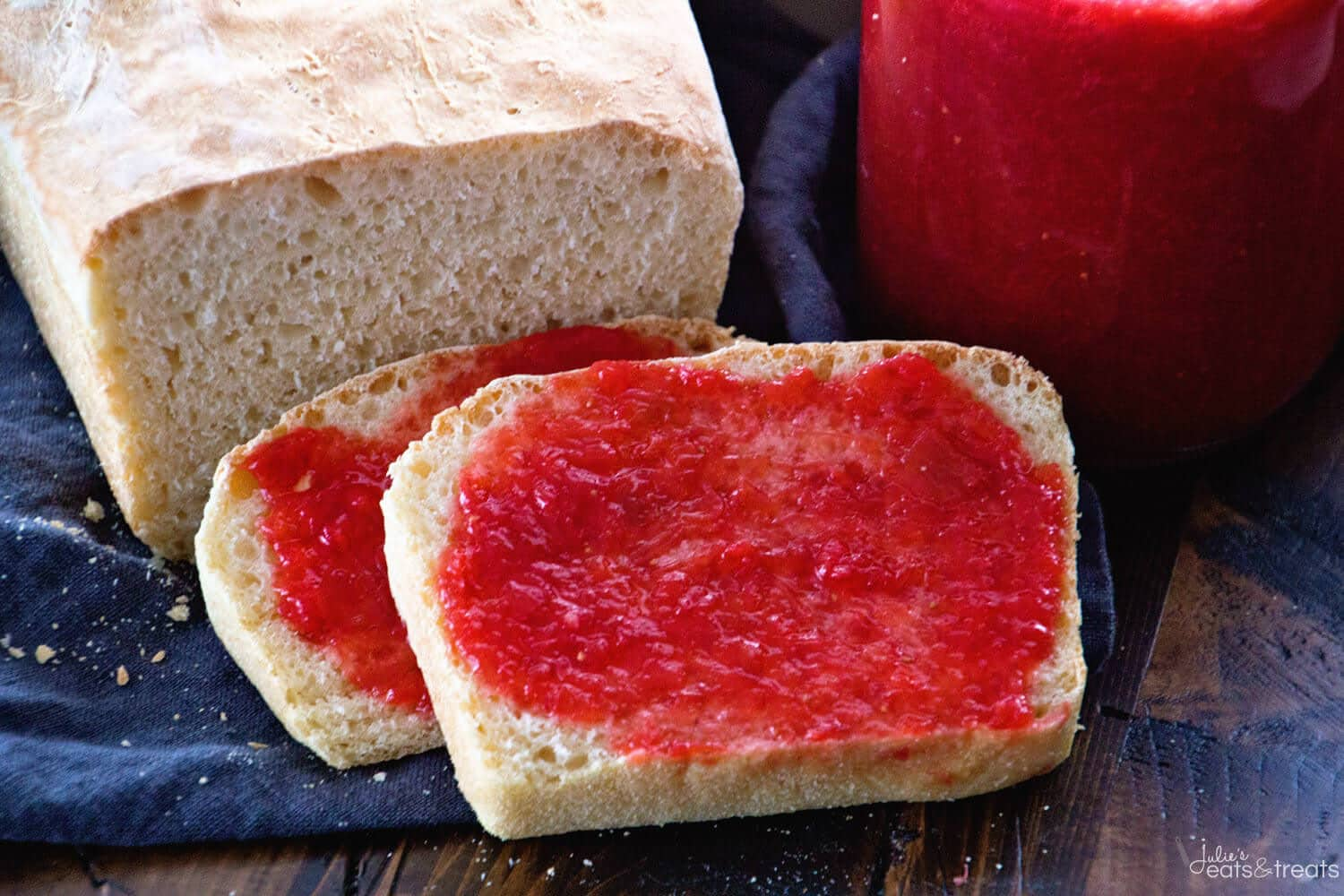 Slices of English Muffin bread with strawberry rhubarb jam on it and jar of jam in background