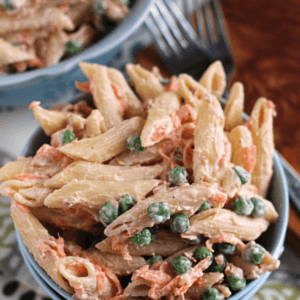 Two blue bowls of bacon ranch pasta salad on decorative cloth napkins