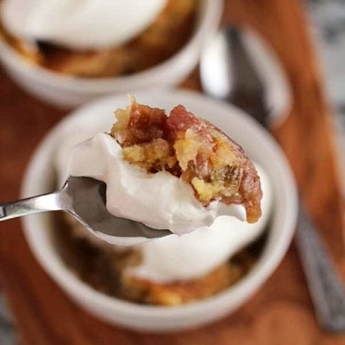 A spoon full of rhubarb crunch and whipped topping being held over two white bowls of rhubarb crunch on a wood board
