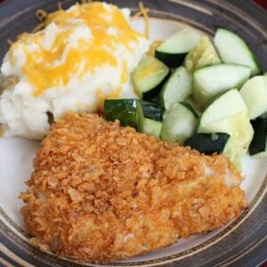 A french's crunchy cheddar onion chicken breast on a plate with mashed potatoes and zucchini
