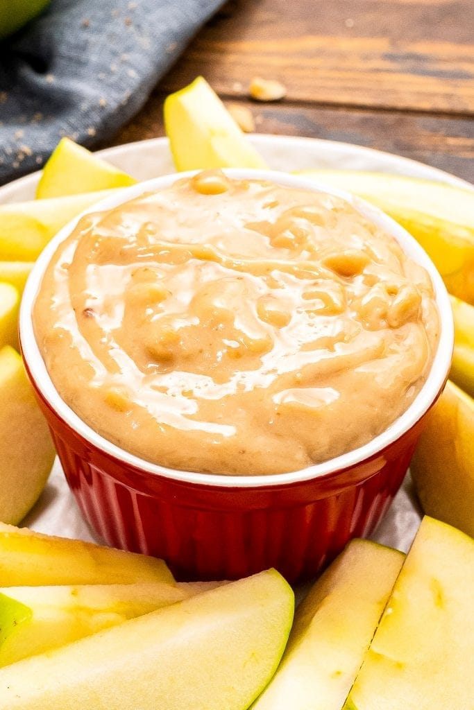 A red bowl on a white plate full of apple brickle dip. Sliced apples arranged on plate around the bowl.