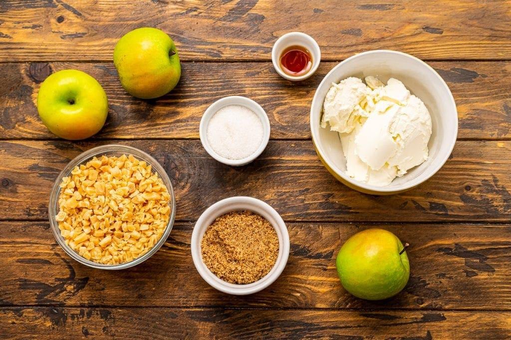 Ingredients in bowls including bowls of brown sugar, toffee pieces, sugar, brown sugar, vanilla and cream cheese.