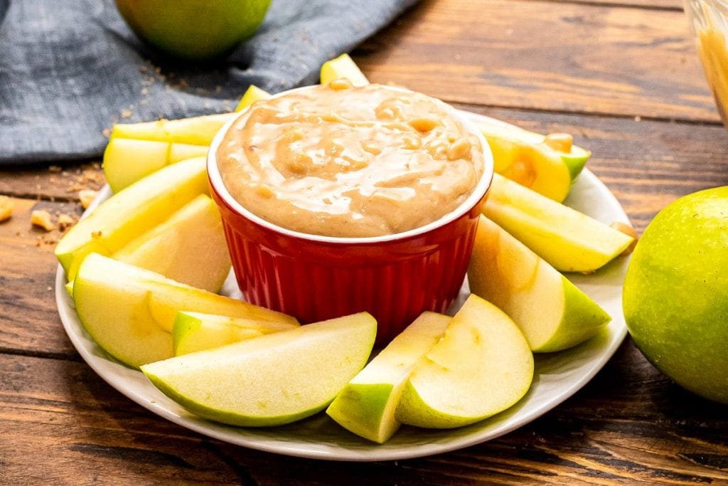 A round plate with slices of apples around a red bowl of apple brickle dip.