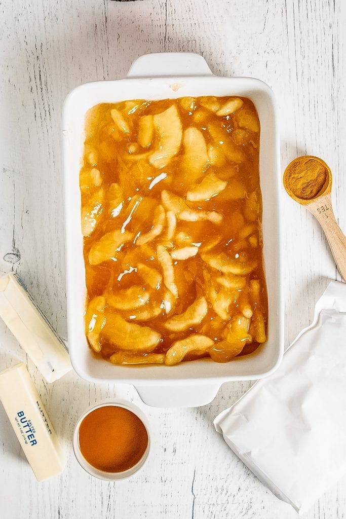 Apple Pie filling in white baking dish with butter sticks, cinnamon and caramel beside it.