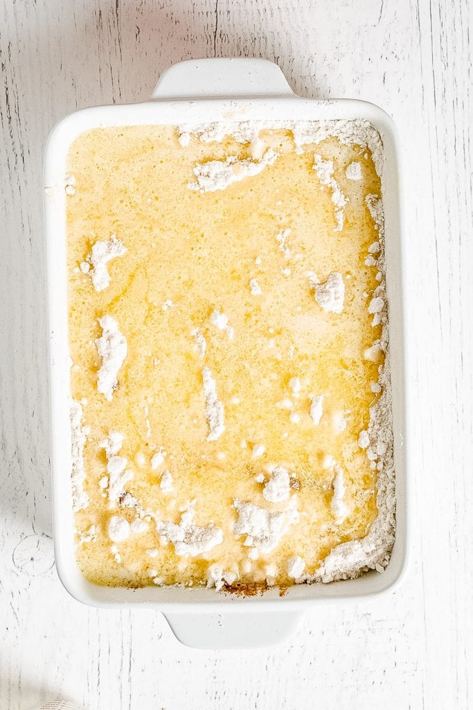 Butter poured over cake mix in white baking dish for cake