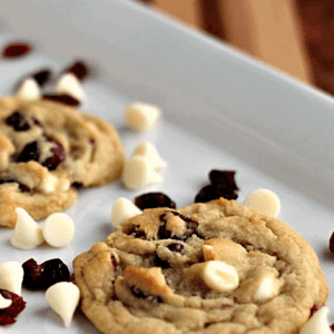 White chocolate cranberry cookies on a white tray with white chocolate chips and dried cranberries