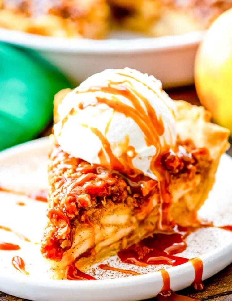 Slice of Apple Pie with crumb topping and ice cream on a plate