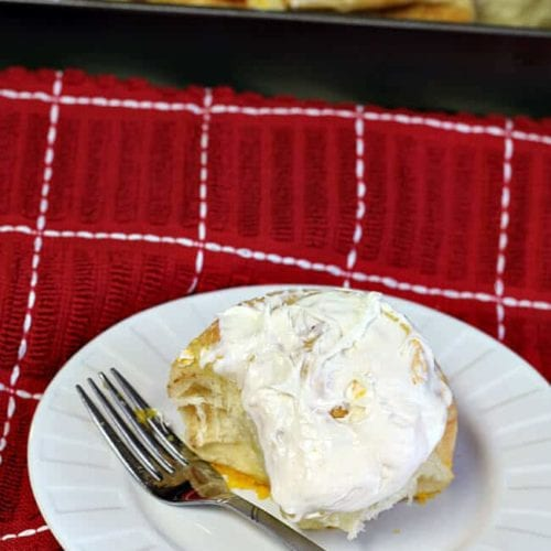 A three ingredient cinnamon roll on a white plate with a fork sitting on a red kitchen towel