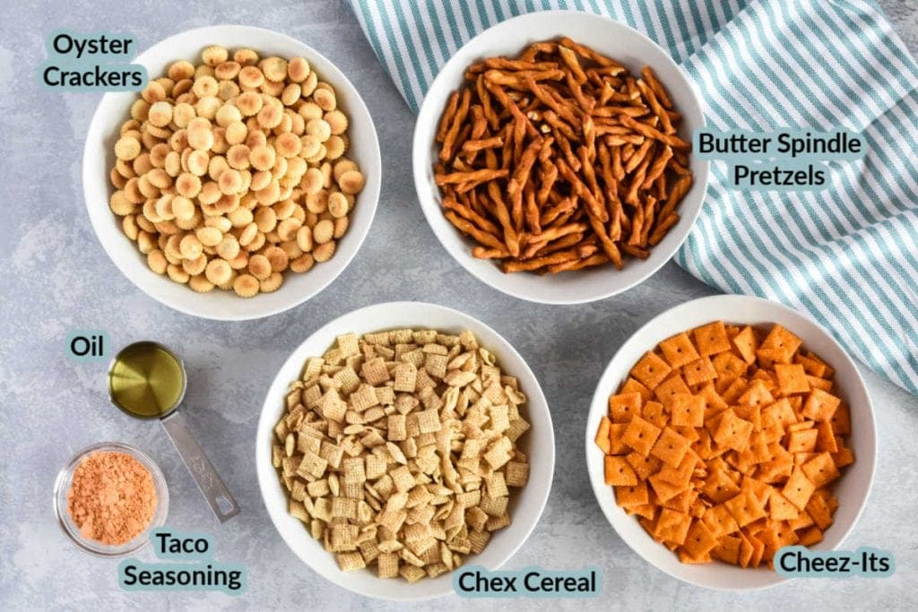 Overhead image with the ingredients to make taco chex mix cheez-its, pretzels, oyster crackers, chex cereal, taco seasoning, oil