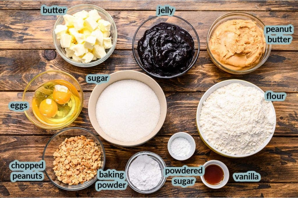 Ingredients to make bars including sugar flour butter peanuts jelly eggs vanilla and more