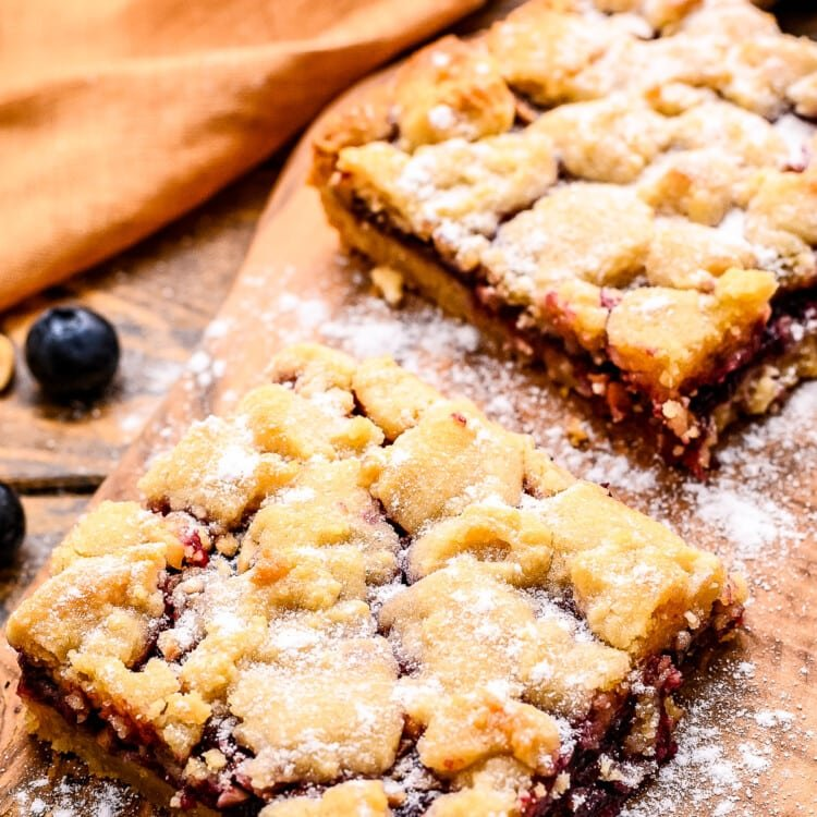 Prepared bars on small wooden cutting board dusted with powdered sugar