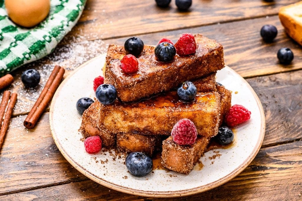 stack of french toast sticks with syrup and berries topping it on a plate