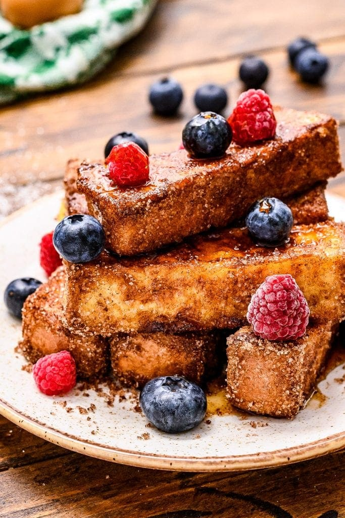Plate with french toast sticks on it and blueberries and rasperries