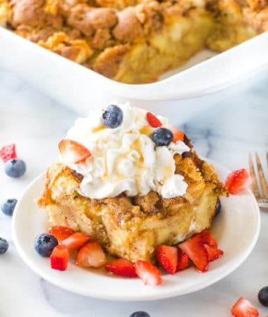 Overnight French Toast Casserole on plate with whipped cream and berries