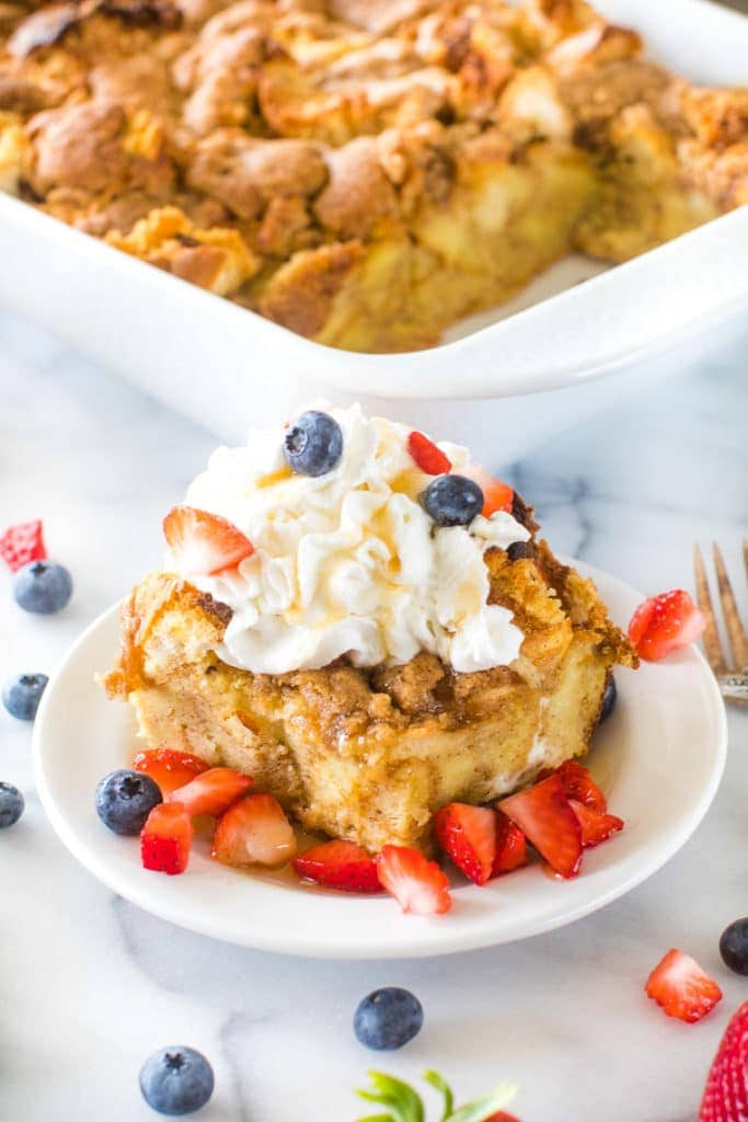 Overnight French Toast Casserole on white plate with berries
