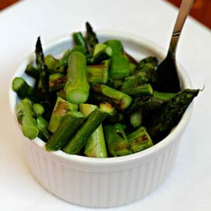 A white bowl of skillet asparagus with a fork in it sitting on a white plate