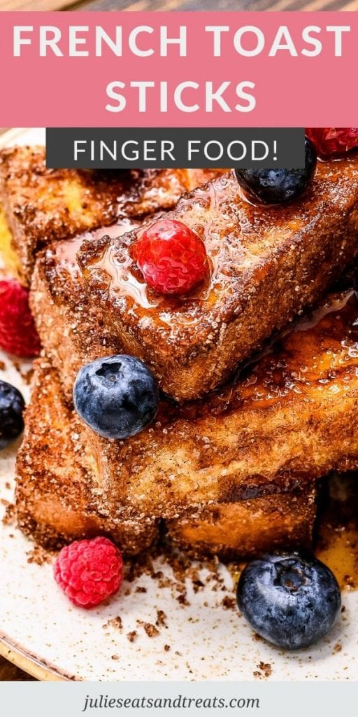 French Toast Sticks topped with syrup and berries on a plate