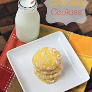 A stack of four lemon cool whip cookies on a square white plate next to a glass of milk