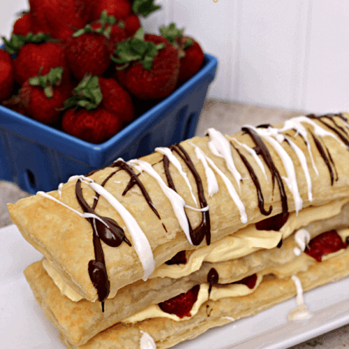 Easy strawberry napoleon on a long white plate with a crate of strawberries in the background