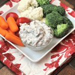 A square white plate with carrots, cherry tomatoes, cauliflower, broccoli, and a bowl of dill veggie dip on it