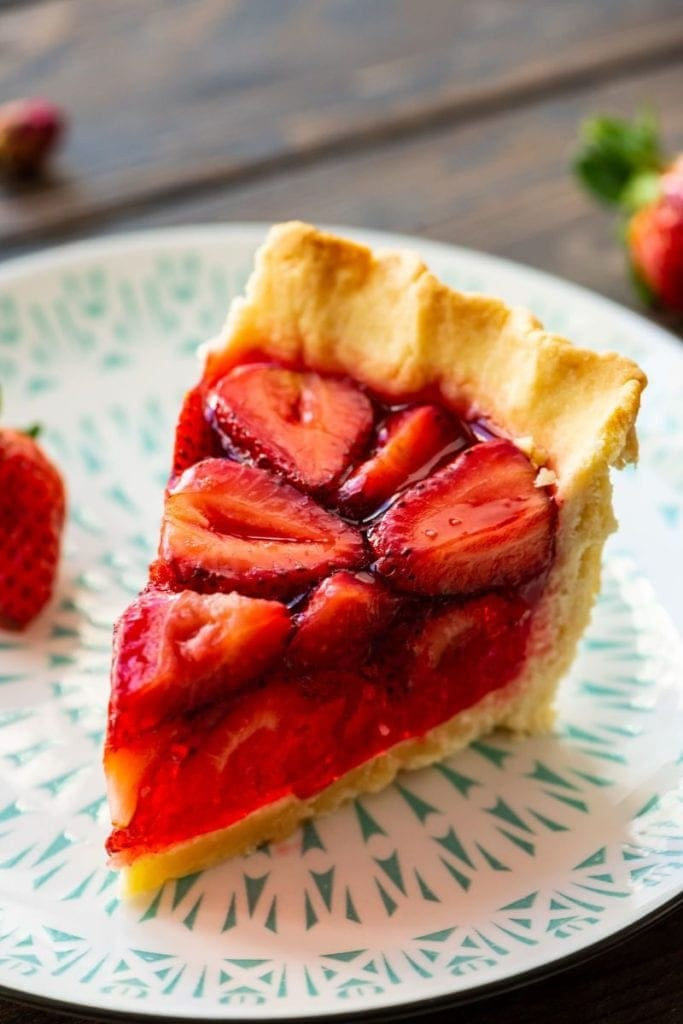 Slice of pie on white and green plate and fresh strawberry in background
