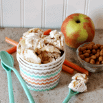 A bowl of apple cinnamon ice cream next to blue spoons, an apple, and a bowl of cinnamon chips