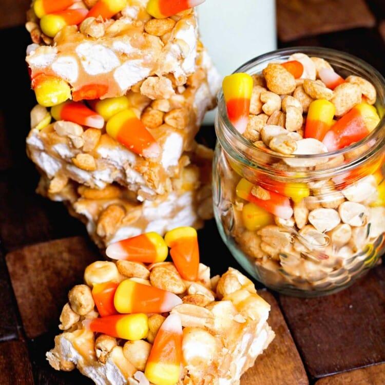 Four candy corn peanut bars on a wood board with a jar of candy corn and peanuts and a jar of milk