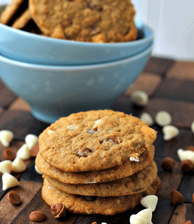 Stack of four cinnamon chip pumpkin cookies on a wood board scattered with cinnamon chips and white chocolate chips and a blue bowl of cookies in the background