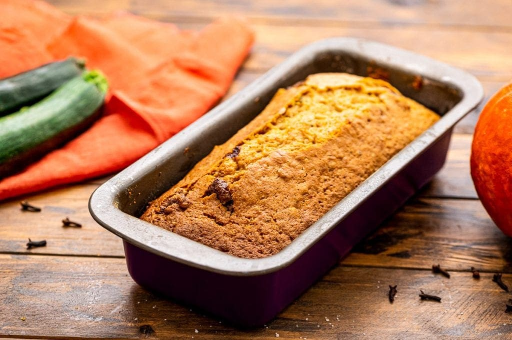 Pumpkin Zucchini Bread Loaf in pan on a wooden background