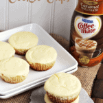 Two caramel macchiato sugar cookie cups stacked on wax paper next to a square white plate with four cups on it and a bottle of caramel macchiato coffee creamer