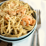 Two blue bowls stacked on a white napkin with the top one full of garlic butter shrimp scampi